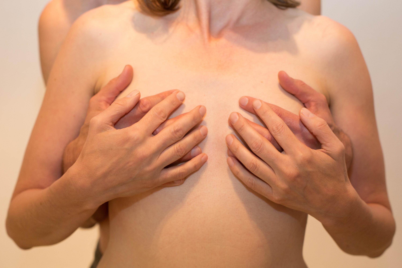 Hände umfassen die Brüste, für Liebe & Sexualität & Brustmassage